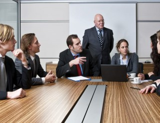 An office meeting between a senior executive and six of his junior staff members